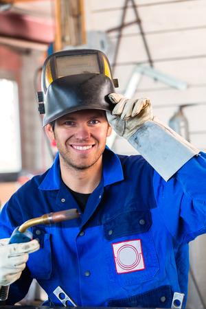 soldador: Soldador con dispositivo de soldadura en el taller de metal