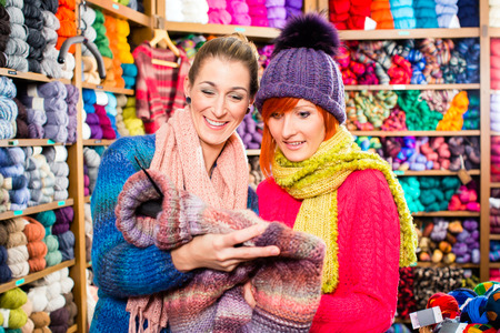 haberdashery: Young women buying colorful pullover in knitwear fashion textile store Stock Photo