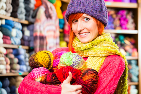 yarn: Young woman buying colorful wool and yarn for their hobby in a knitting shop Stock Photo