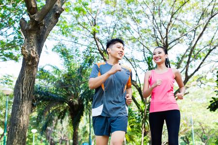 Asiatisk kinesisk man och kvinna joggning i stadsparken Stockfoto