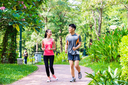 recreation: Asian Chinese man and woman jogging in city park