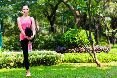 warm up: Asian Chinese woman stretching muscles for fitness in city park Stock Photo