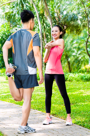 warm up: Asian Chinese man and woman stretching muscles in park for sport fitness Stock Photo