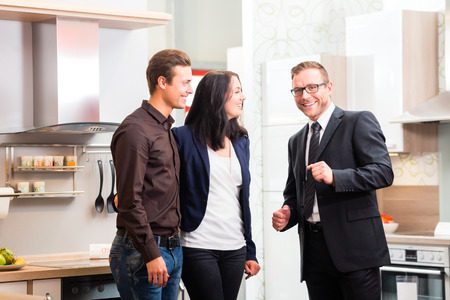 furniture store: Man and woman consult salesman for domestic kitchen in studio or furniture store