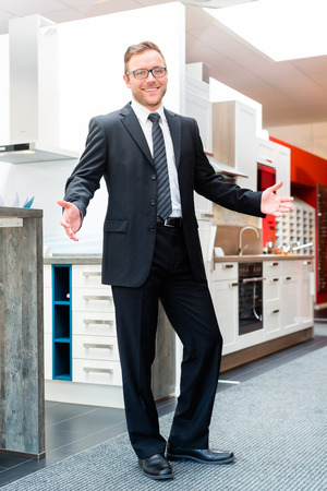 fitted: Salesman in domestic kitchen in studio or furniture showroom