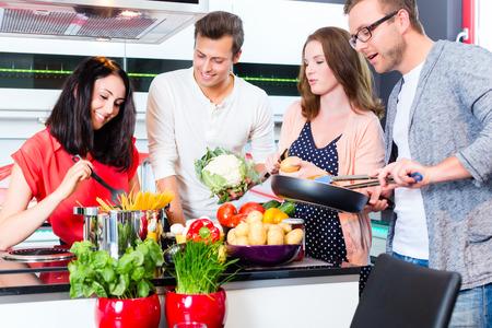 mujeres cocinando: Amigos que cocinan espaguetis y carne en la cocina dom�stica