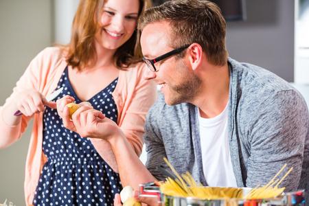 mujeres cocinando: La mujer y el hombre para cocinar espagueti en la cocina dom�stica