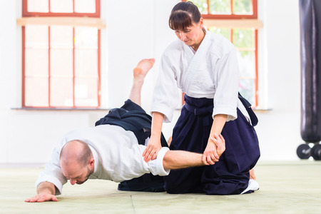 martial art: Man and woman fighting at Aikido training in martial arts school
