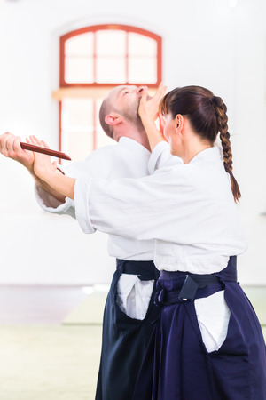 self  discipline: Man and woman fighting with wooden knifes at Aikido training in martial arts school