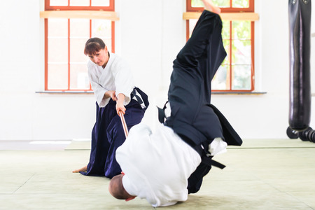 martial arts woman: Man and woman fighting with wooden stick at Aikido training in martial arts school