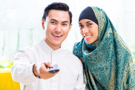 Aziatische moslim man en vrouw televisie kijken in de woonkamer Stockfoto