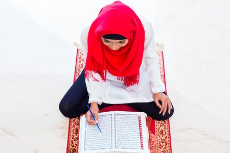 koran: Asian Muslim woman reading Koran or Quran on praying carpet wearing traditional dress