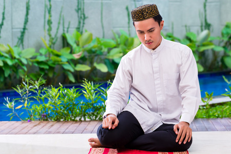 praying: Asian Muslim man praying on carpet wearing traditional dress