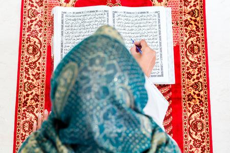 woman praying: Asian Muslim woman reading Koran or Quran on praying carpet wearing traditional dress