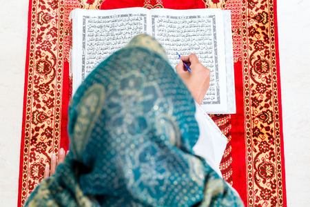 mujer rezando: Mujer musulmán asiática que lee el Corán o el Corán en la oración de la alfombra con un vestido tradicional