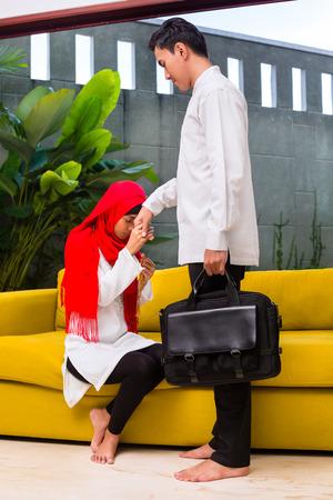 honoring: Asian Muslim woman honoring man in living room wearing traditional dress Stock Photo