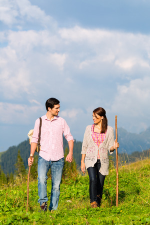 couple of man and woman hiking on mountain summit or alpine grassland in the Bavarian Alps, enjoys the panorama in the leisure time or in vacation photo