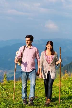 Couple on fitness hiking vacation on mountain summit or alpine grassland in the Alps photo