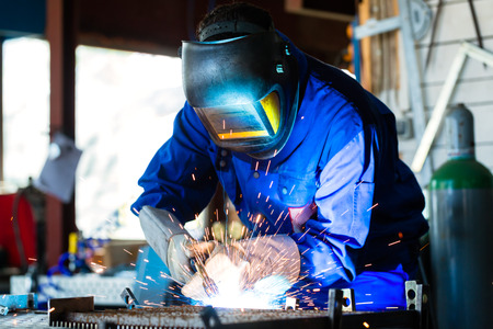 metal working: Welder bonding metal with welding device in workshop, lots of sparks to be seen, he wears welding googles Stock Photo
