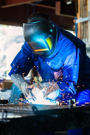 soldadura: Soldador de metal pegado con el dispositivo de soldadura en el taller, un mont�n de chispas para ser visto, lleva googles soldadura