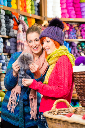 bobble: Young women buying colorful bobble hat in knitting fashion textile store Stock Photo