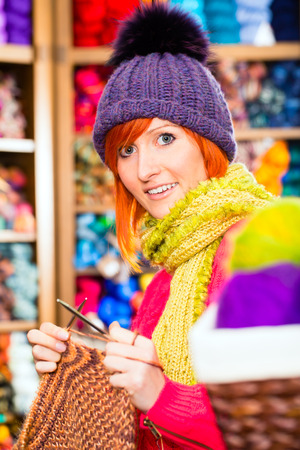 haberdashery: Young woman or saleswoman in knitting shop showing or explaining how to knit with circular needle