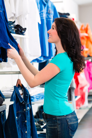 choosing clothes: Woman buying fashion blue jeans in shop or store Stock Photo