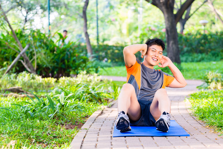 six pack: Asian man doing crunches for six pack training in park