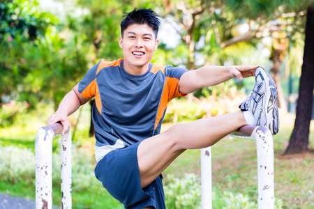 stretching exercise: Asian man stretching muscles for fitness in outdoor gym