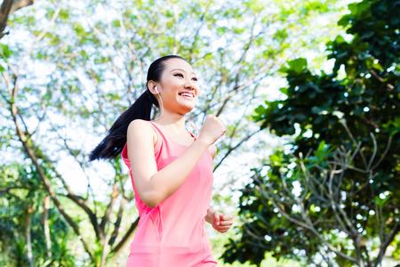 Asian woman runner jogging in city park