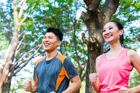 personas trotando: Hombre chino asi�tico y una mujer corriendo en el parque de la ciudad Foto de archivo