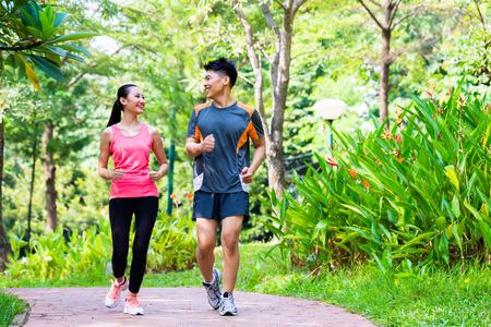 atleta corriendo: Hombre chino asiático y una mujer corriendo en el parque de la ciudad Foto de archivo
