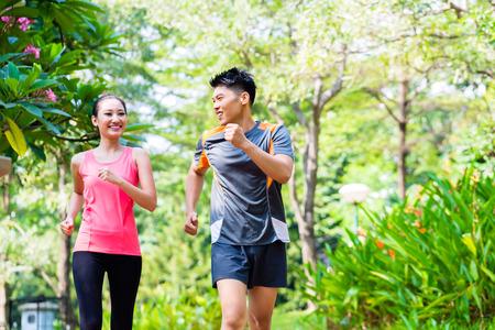 pareja saludable: Hombre chino asi�tico y una mujer corriendo en el parque de la ciudad Foto de archivo