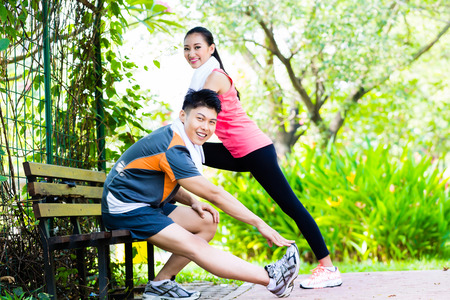 Asian Chinese man and woman stretching muscles on park bench Stock Photo - 33751318