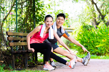 Asian Chinese man and woman stretching muscles on park bench