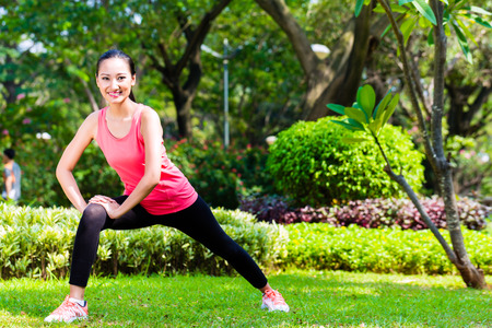 warm up exercise: Asian Chinese woman stretching muscles for fitness in city park Stock Photo