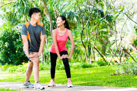 Asian Chinese man and woman stretching muscles in park for sport fitness Stock Photo