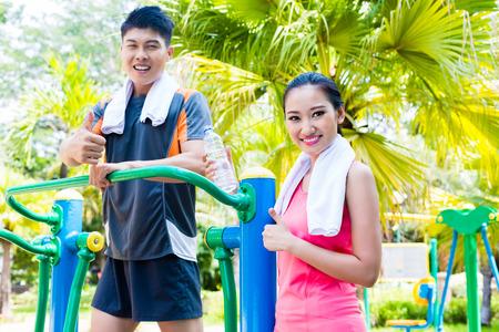 アジアの中国の男性と女性のボディービルのトレーニング屋外ジムで公共のクロス トレーナーに 写真素材