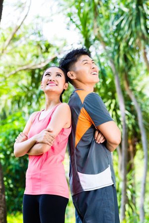 take a break: Asian Chinese man and woman take a break after fitness jogging in city park