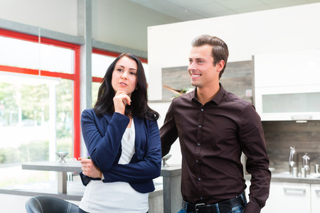 furniture store: Man and woman buying domestic kitchen in studio or furniture store