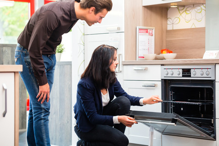 Man and woman buying domestic kitchen in studio or furniture store showroom