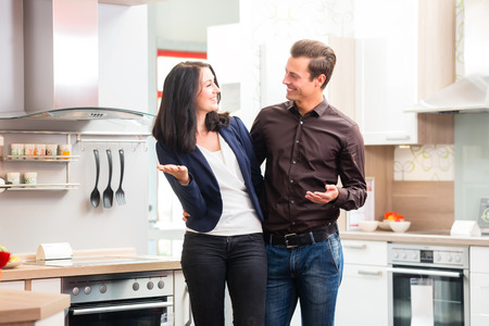 buying: Man and woman buying domestic kitchen in studio or furniture store