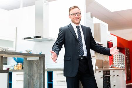 Salesman in domestic kitchen in studio or furniture showroom