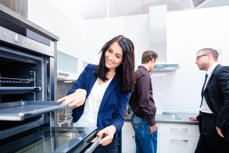 Woman picking oven for domestic kitchen in studio or furniture store photo
