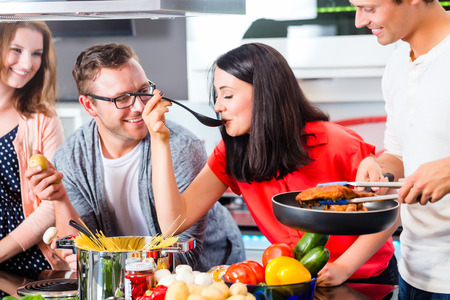 cocineros: Amigos que cocinan espaguetis y carne en la cocina doméstica