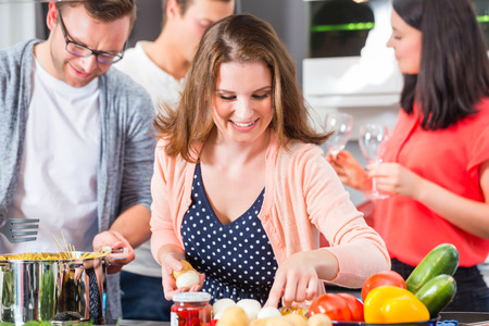 Friends cooking pasta and meat in domestic kitchen photo