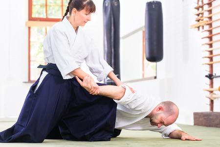 self  discipline: Man and woman fighting at Aikido training in martial arts school