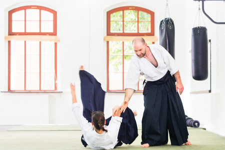 Man and woman fighting at Aikido training in martial arts school photo