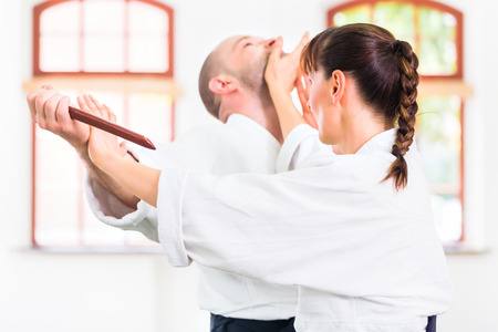 武道の学校の合気道の稽古でナイフ男と女と木製の戦い 写真素材