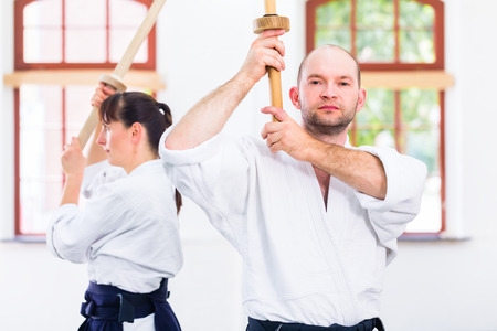 self  discipline: Man and woman fighting with wooden swords at Aikido training in martial arts school